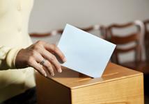 Hånd som legger en stemmeseddel i boksen